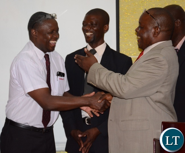 Lusaka District Commissioner Capt. Davidson Mulenga having a light moment with Shoprite General Manager Charles Bota (l) Integrated Community Anti-Litter Initiative Chairperson Pascal Chikumbi during he signing of MOU on litter and waste disposal awareness campaign between ZANAMACA and ICALI