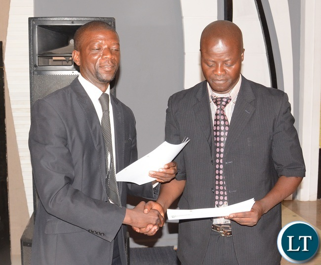 Zambia National Marketers Credit Association (ZANAMACA) President Frank Kameya exchange documents after signing with Integrated Community Anti-Litter Initiative Chairperson Pascal Chikumbi during the signing ceremony of MOU on litter and waste disposal awareness campaign between ZANAMACA and ICALI