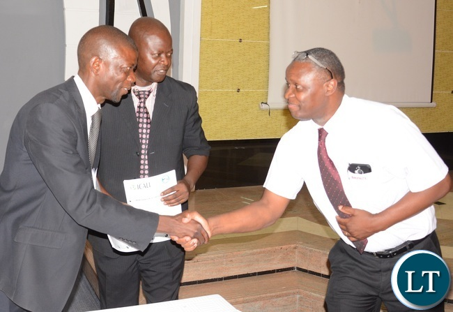 Integrated Community Anti-Litter Initiative Chairperson Pascal Chikumbi shake hands with Shoprite General Manager Charles Bota whilst Zambia National Marketers Credit Association (ZANAMACA) President Frank Kameya looks on during the signing ceremony of MOU on litter and waste disposal awareness campaign between ZANAMACA and ICALI
