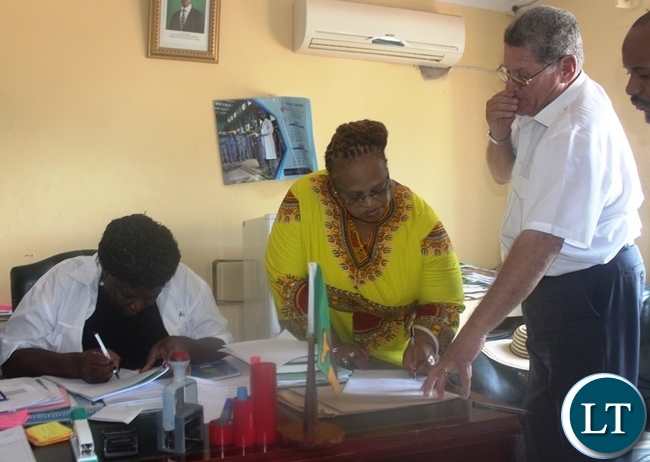 Central province PS Daisy Ng'ambi (left) and Radixus (PTY) Ltd chairperson noluthando SHweni signing a memorandum of understanding to signify the construction of ultra-modern Airport in Itezhi-Tezhi district of central province. Looking on is Radixus (PTY) Ltd chief of operations Eugene Labuschagne