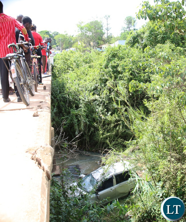 Passserby's look at the car that plunged into Mansa river