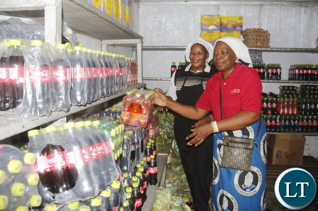 n red St Ignatius Parish Council Vice Chairperson Bernadette Mulenga and UTH Stores Lady Ireen Mumba Dihanga trying to arrange some foodstuffs donated in the UTH kitchen cold room.