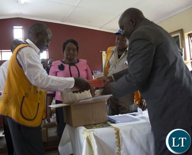 Mukuba Lions Club President, Emmanuel Kangwa in yellow west coart hand over 20,000 copies of books worthy K1.5million to Kitwe University College of Education Principal, Andrew Mutobo who received the donation on behalf of selected primary and secondary schools and colleges in kitwe.