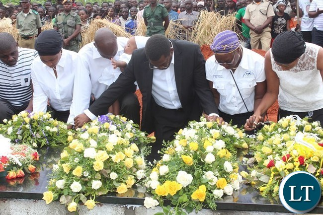 CHILDREN of the late former Deputy Speaker of the National Assembly, Mkhondo Lungu, led by their eldest brother, Muhabi ( in black suit) pray after laying wreaths at the grave of their father at Kachule farm in Lundazi