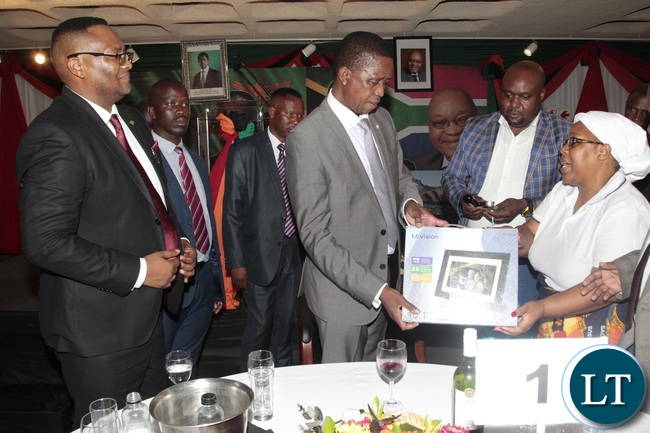 President Edgar Lungu is presented with a digital calendar with memories and pictures of him by Patriotic Front (PF) South Africa branch chairman Mr Sydney Njamba (centre) and his Vice chairperson Rita Zulu (right) during a dinner to meet Zambians living in South Africa held at the Zambian Embassy in Pretoria, South Africa.looking on is Zambian Ambassador to South Africa Emmanuel Mwamba