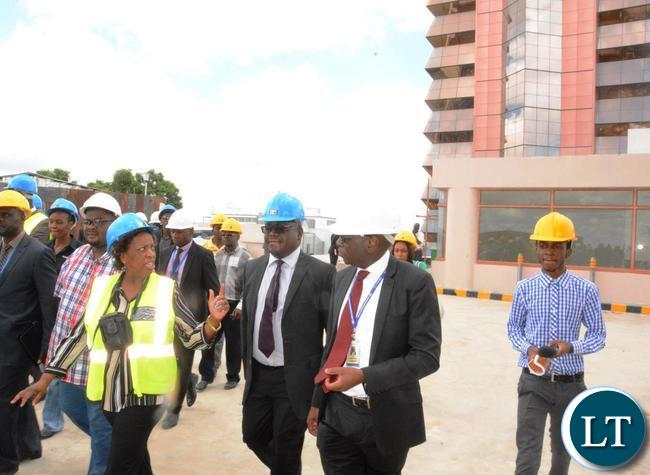 Minister of Labour Joyce Simukoko (in yellow reflector) flanked by National pension Scheme Authority Director General Yollard Kachinda (2nr) and Zambia National building Society Managing Director Joseph Chikolwa (third from right) touring the Society Business Park  in Lusaka