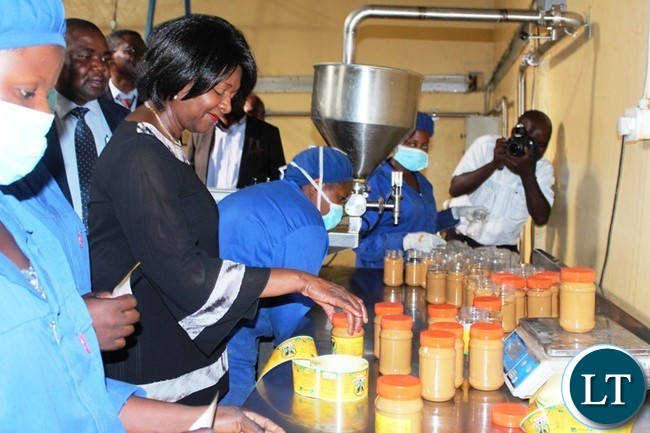 COMMERCE Minister, Margaret Mwanakatwe, admires the packaging of peanut butter at Community Market for Conservation (COMACO) in Chipata on Thursday when she toured the processing plant. PICTURE BY STEPHEN MUKOBEKO/ZANIS