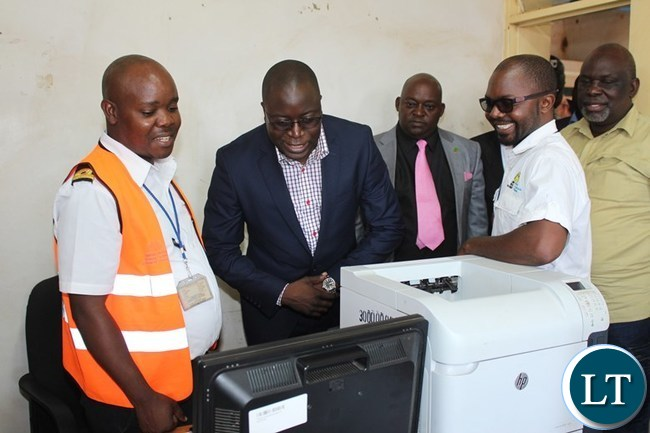 EASTERN Province Minister, Makebi Zulu (in black suit) looks at the Zambia Revenue Authority (ZRA) Automated System for Customs Data (ASYCUDA) at Chanida border post on Tuesday. Looking on are ZRA Chanida border post Customs Officer, Elias Mwanda (l), Chadiza District Commissioner, George Phiri ( third from left), ZRA Chanida border post Acting Station Manager, Peter Nyirenda ( second right) and Chadiza Member of Parliament, Salatiel Tembo, far right. PICTURE BY STEPHEN MUKOBEKO/ZANIS