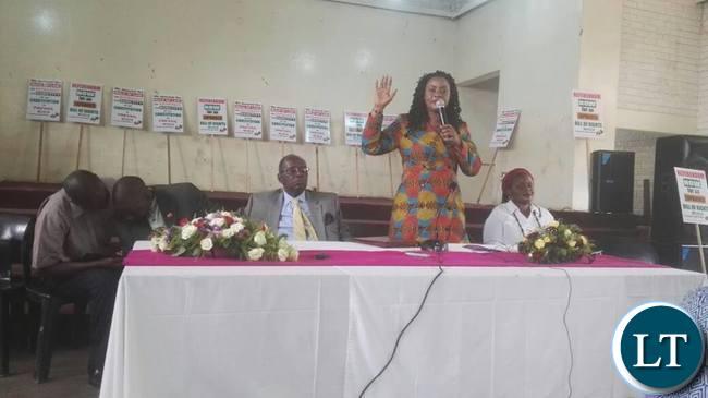 Pamela Chisanga speaks during the launch whilst Bishop Mambo and Judith Mulenga look on