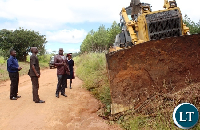 Mbala District Commissioner Kedrick Sikombe (right) and Mayor Brighton Sindeya (brown suit) inspects the newly constructed 10.4km township roads in today. The Leadership expressed happiness workmanship exhibited by China CAMC.:- picture by Mary Bwembya (ZANIS).