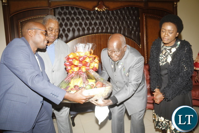 KK receiving from RB a basket of fruits while looking are RBs wife Tandiwe Banda and KK grand son Mazuba Kaunda (at the far left) on his 93rd birthday at his home in State lodge area