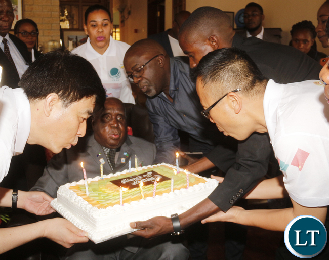 KK receiving a cake donated to him by Zambia China Association messengers on his 93rd birthday at his home in State lodge area.