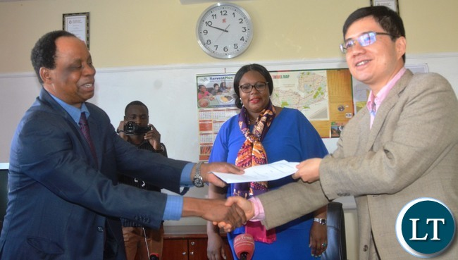 Ministry of Agriculture Permanent Secretary Julius Shawa exchange document with Avic Limited Representative Cui Ji just after the signing of a Memorandum of Understanding to construct a New National Resource Development(NRD) College in chief Shakumbila's village in Mambwa district while the Minister of Agriculture Dora Siliya looks