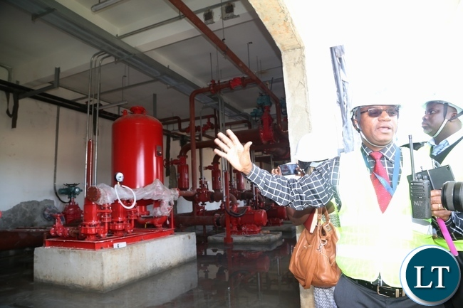 Ariel Phiri Manager Projects at Kenneth Kaunda International Airport showing Journalists water pimps at the new fire station