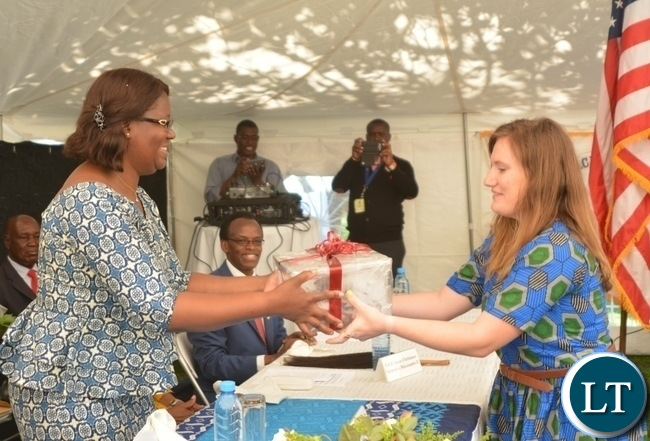 Peace Corp Volunteer Alison Flenniken(r)  presents a gift of appreciation to the Minister in the Office of the Vice President Sylvia Chalikosa(l)  at the Peace Corps Swearing in Ceremony for Environment and Aqua-Culture Volunteers in Lusaka