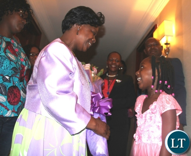 First Lady Esther Lungu receives a bouquet of flowers from Miss. Kalimina, Daughter of Mrs. Christine Kalimina the Deputy representative to the un on  arrival at Palace Hotel