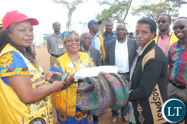 Lions Club Governor for District 413 Zambia, Ms Jess ica Choobe, handing over the donated materials to  the refugee leader at Kenani refugee transit centre.