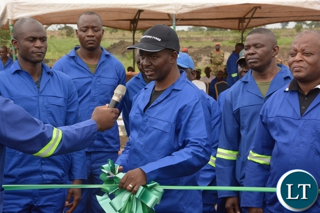 Zambia Army, Chief of Cooperatives Resettlement and Estates Brigadier General Charles Shapi flanked by Zambia Army Personnel cutting the ribbon to officially launch the 2017-2018 planting at 2ZR Makeni Farm