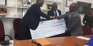 Hon. Mutati receives a dividend cheque from Hon. Mushimba on behalf of Zambia Airports Corporation