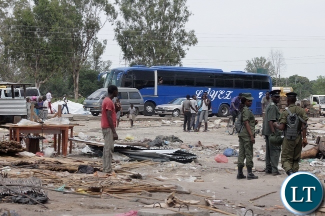 Zambia Police Officers stand guard during the demolition exercise and closure of Kaoma-Kaoma Market make-shift structures as a preventive measure against the outbreak of Cholera in Mongu