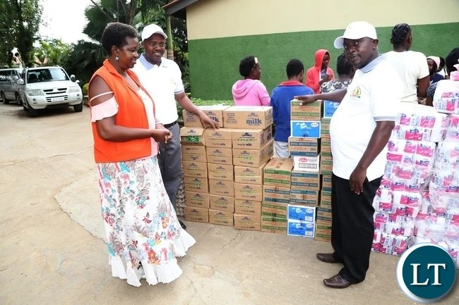 Association of Burundian Residents In Zambia Chairperson Dieudonne Baranzira flanked by His Vice Chairperson Emile Masabarakiza showing the donated goods to Kabwata Orphanage goods worth K 30,000 to the founder Angela Miyanda during the donation