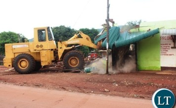 A Front end loader from Chipata City Council demolishes an illegal structure allegedly built on top of an Eastern Water and Sewerage Company water pipe near Kapata Market in Chipata. This was during a cleanup exercise to curb the spread of cholera in the district. PICTURE BY STEPHEN MUKOBEKO/ZANIS