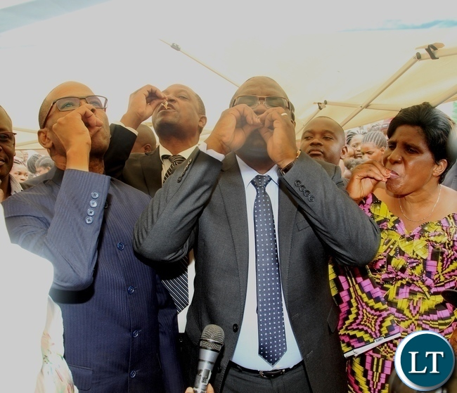 Minister of Health Dr Chitalu Chilufya (centre) , Kanyama area member of parliament Elizabeth Phiri (right) and deputy Secretary to Cabinet Patrick Mvunga (left)taking the oral cholera vaccine to officially launch the vaccine in Kanyama Mutanda bantu