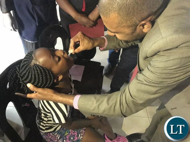 Minister of Local Government Vincent Mwale administering Cholera vaccine