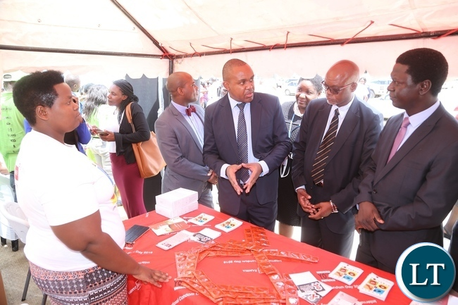 AIDS Heath Foundation Country Director Dr. Mabvuto Kango stress a point on the condoms to Ministry of Health Director Public Health Dr. Andrew Silumesii (r) and Acting Director General National AIDS Council Fortune Chibamba (2nr) whilst exhibitor Mary Chazangwe looks on during the International Condom Day tour of stands at Central Mal
