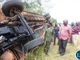 Part of the onlookers catches a glimpse of a Juldan coach Reg. No ABE 6940 which has claimed 4 lives after over turning due to allegedly failure by the driver to stop on the T-Junction along the Kasama- Luwingu road in the early hours of Monday. The driver is among the 3 men who died on the spot while one female died upon arrival at the Hospital.-Picture by Mary Bwembya (ZANIS).