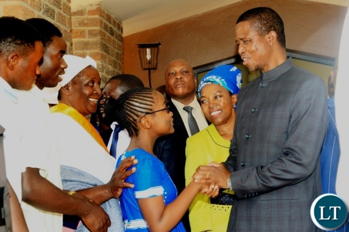 President Edgar Lungu greets a girl after a church service at Saint Marys Assumption Parish in Chilanga.looking on (center) is PF chilanga Constituency member of Parliament candidate Mrs Mary Langa