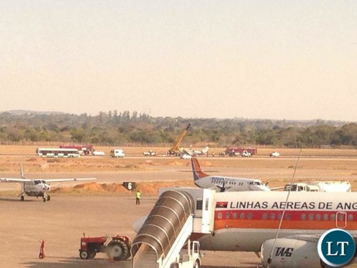 Airport authorities using a large crane to lift a plane off a runway at Kenneth Kaunda International Airport in Lusaka