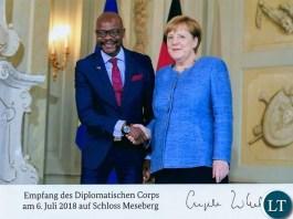 Images, chancellor Merkel shakes hands with Zambia Ambassador Mukwita,