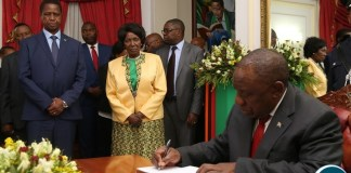 South African President His Excellency Mr.Cyril Ramaphosa signs a visitors book while President Edgar Lungu and Vice President Inonge Wina looks on at State House