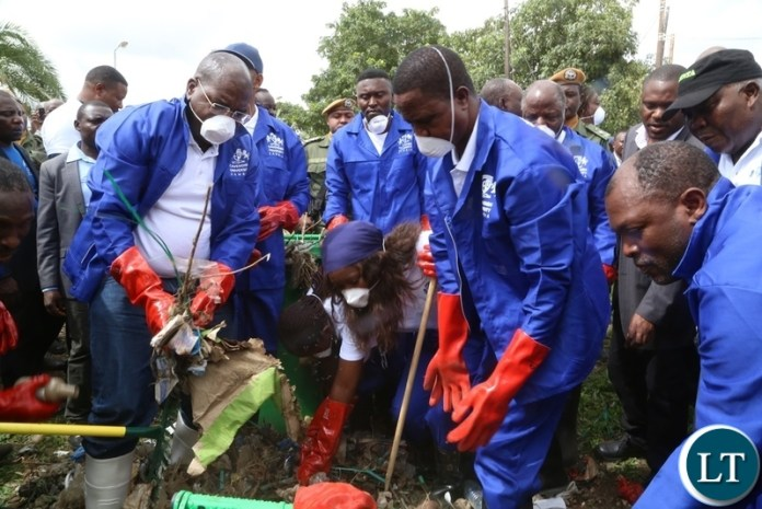 President Edgar Lungu and Minister of Health Chitalu Chilufya cleaning during the Cavendish University Keep Zambia Clean, Health and Green at Kafue Roundabout