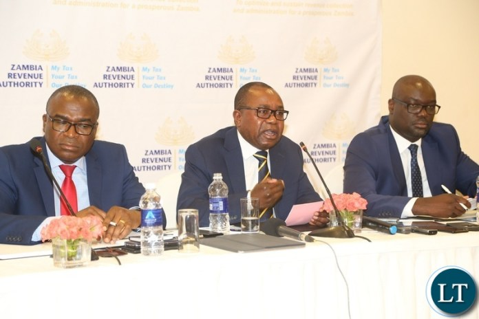 Zambia Revenue Authority (ZRA) Commissioner General Kingsley Chanda flanked by Commissioner Domestic Taxis Moses Shuko (l) and Commissioner Customs Sydney Chibbabbuka speaking to journalists during the press conference at Pamodzi Hotel