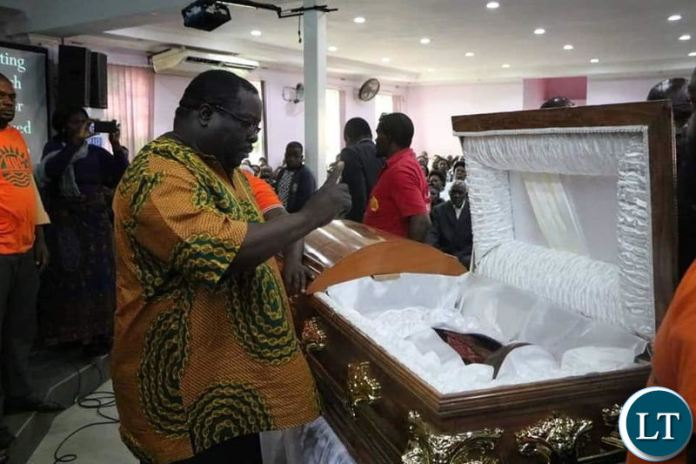 NDC Leader Chishimba Kambwili waves the party symbol at late Obed Kasongo's body during body viewing at Northmead Assemblies of God