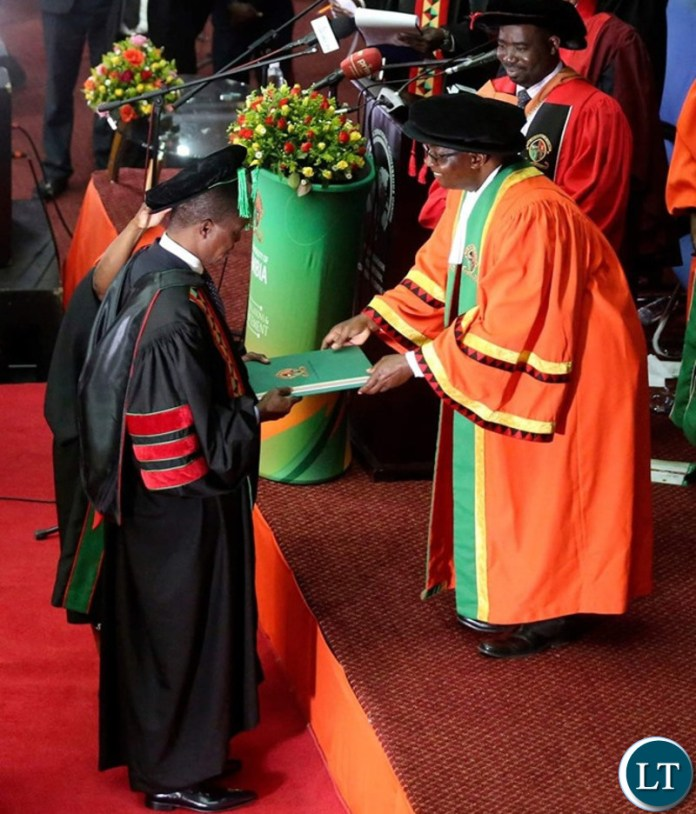 President Edgar Chagwa Lungu (left) receives the Honorary Doctor of Laws Degree Certificate from University of Zambia Chancellor Prof.Luke Mumba (right) at Mulungushi International Conference Centre during the University of Zambia's 48th Special Convocation Ceremony on Saturday,June 29,2019. PICTURE BY SALIM HENRY/STATE HOUSE ©2019