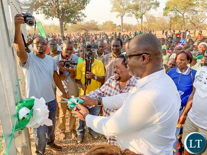 Msanzala Member of Parliament Peter Daka gets assistance in cutting a ribbon to symbolise the launch of a communication tower at Penja-Penja Village in Petauke