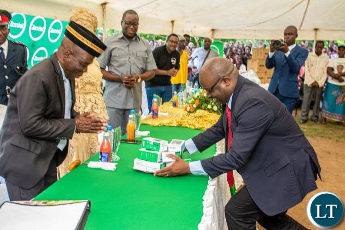 Zamtel CEO Sydney Mupeta hands over some low cost handsets to Chief Mukanya of the Kunda people of Mambwe District during the commissioning of the communications tower in the area