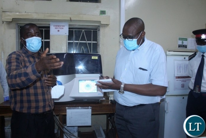 Ministry of Health Technical Services Permanent Secretary Dr. Kennedy Malama (r) taking notes as Lewanika General Hospital Principal Biomedical Scientist Chiswamo Phillips explains (l) during the tour of health facilities in Mongu