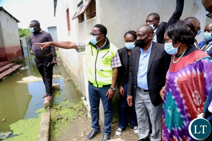 DMMU National Coordinator Chanda Kabwe showing the flooded area to the Vice President Inonge Wina during the tour of the flooded kuku compound