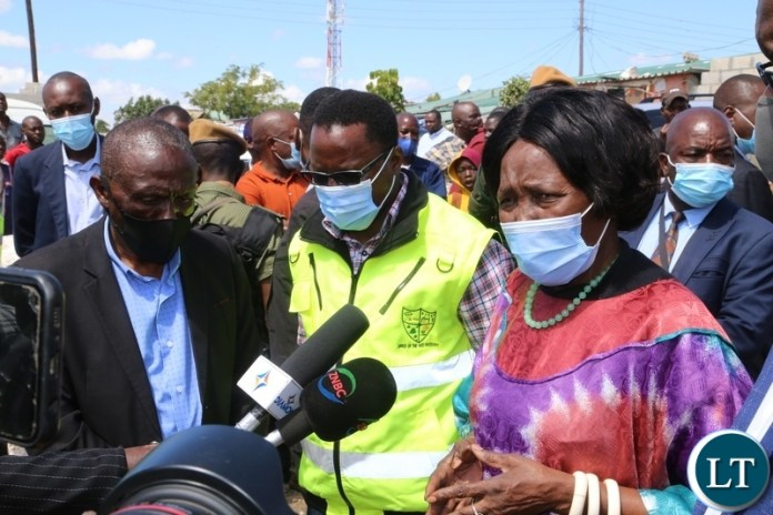 Vice President Inonge Wina speaking to journalists whilst DMMU National Coordinator Chanda Kabwe and Minister Chiefs Lowrance Sichalwe during the tour of the flooded kuku compound