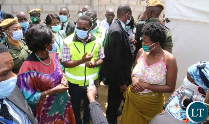 Vice President Inonge Wina flanked by DMMU National Coordinator Chanda Kabwe confers with the flood during the tour of Kuku compound