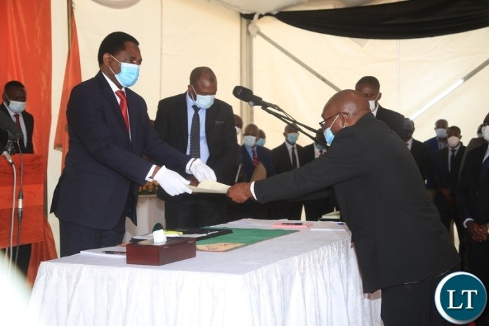 PRESIDENT Hakainde Hichilema receives an affidavit form from Newly sworn in Minister of Defence Hon.Ambrose Lufuma at swearing -in ceremony in Lusaka