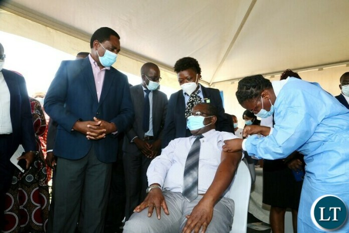 Health Personnel Mutinta Habaalu giving a vaccine ejection to His Royal Highness Senior Chief Luembe whilst President Hakainde Hichilema looks on during the relaunch of COVID-19 vaccine at OYDC