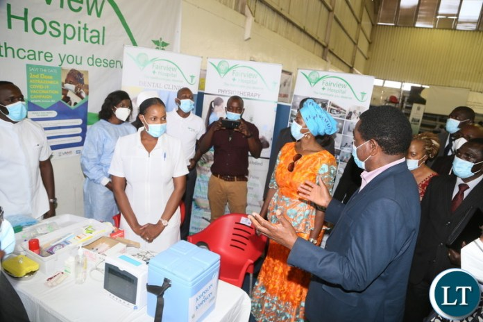 President Hakainde Hichilema confers with nurses when he toured the stands during the relaunch of COVID-19 vaccine at OYDC