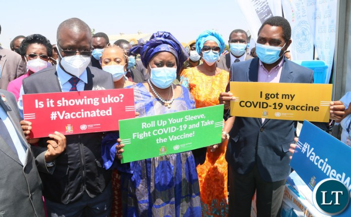 President Hakainde Hichilema with UN country coordinator Caumba Mar Gadio  and Dr. Nathan Bakayta hold high the placards  during the relaunch of COVID-19 vaccine at OYDC