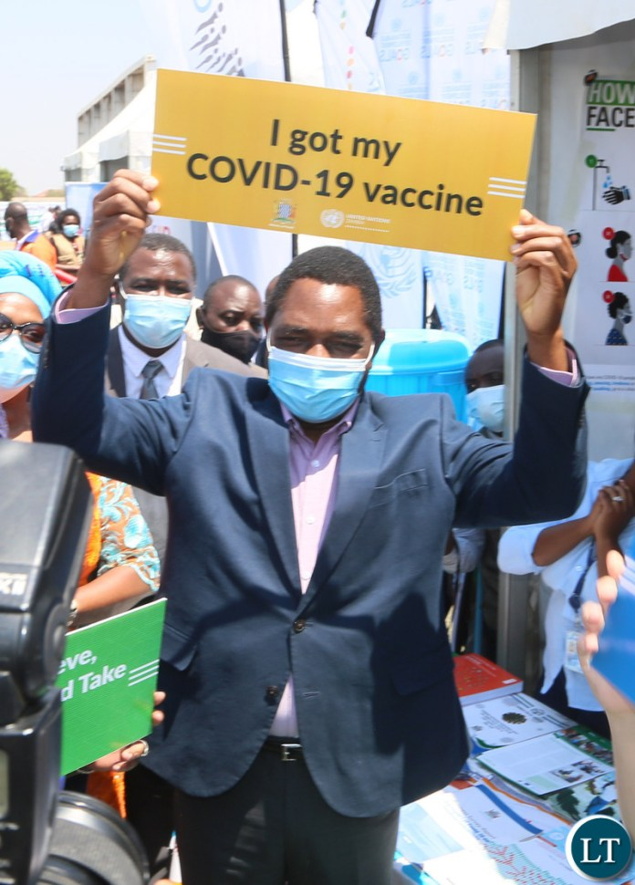President Hakainde Hichilema hold high a placard showing is vaccinated during the relaunch of COVID-19 vaccine at OYDC
