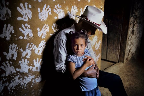 A man and his granddoughter in front of a wall decorated with hand prints, La Fortuna, Honduras, 2004 | photo by Steve McCurry